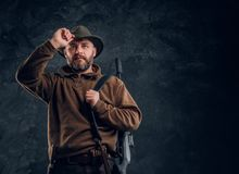 Portrait of a bearded hunter with rifle holding hand on hat and looking sideways. Studio photo against a dark wall royalty free stock photos