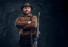 Portrait of a bearded hunter with rifle posing with his arms crossed. Studio photo against a dark wall background royalty free stock photography
