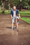 Portrait of a bearded male with a haircut dressed in casual clothes riding a bicycle in a park. Portrait of a bearded male with a haircut dressed in casual royalty free stock images