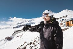 Portrait bearded male skier aged against background of snow-capped Caucasus mountains. An adult man wearing ski googles stock photos