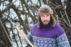Portrait of a Bearded Man with an ax in his hand. Brutal bearded man with an ax. North bearded man with an ax in the woods Royalty Free Stock Photography