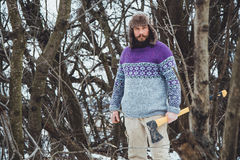 Portrait of a Bearded Man with an ax in his hand. Brutal bearded man with an ax. North bearded man with an ax in the woods Royalty Free Stock Photos