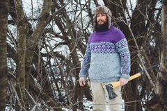 Portrait of a Bearded Man with an ax in his hand. Brutal bearded man with an ax. North bearded man with an ax in the woods Royalty Free Stock Images