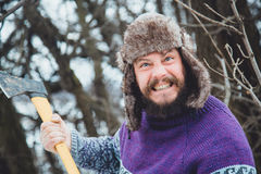 Portrait of a Bearded Man with an ax in his hand. Brutal bearded man with an ax. North bearded man with an ax in the woods Royalty Free Stock Photo