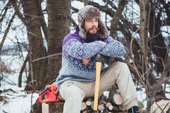 Portrait of a Bearded Man with an ax in his hand. Brutal bearded man with an ax. North bearded man with an ax in the woods Stock Photos
