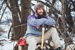 Portrait of a Bearded Man with an ax in his hand. Brutal bearded man with an ax. North bearded man with an ax in the woods Royalty Free Stock Image