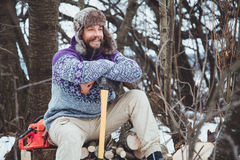 Portrait of a Bearded Man with an ax in his hand. Brutal bearded man with an ax. North bearded man with an ax in the woods Stock Image