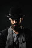 The portrait of bearded man in a bowler hat. The portrait of brutal bearded man in a black bowler hat royalty free stock images