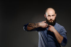 Portrait of a bearded man cutting his beard with scissors. Muscular man with a beard cuts his beard with scissors. He is dressed in a blue shirt. Has a tattoo on royalty free stock photo