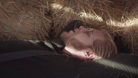 Portrait of bearded man in glasses with laying in the hay with a straw in the mouth close up. Young thoughtful farmer. Resting after hard working day stock footage