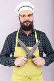 Portrait of a bearded man holding two big sharp knives Royalty Free Stock Photo