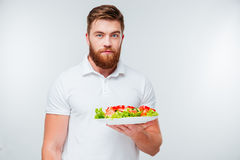 Portrait of a bearded man holing plate with fresh salad Stock Photos