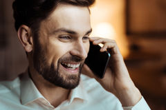 Portrait of bearded man that listening his interlocutor. Nice to hear you. Attractive brunette male person expressing positivity and speaking on telephone while Stock Photography