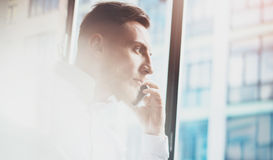 Portrait of bearded man making mobile call at working place.Guy sitting in chair and looking out the panoramic window Royalty Free Stock Image