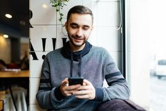 Portrait of bearded man with mobile phone in cafe. Portrait of man with mobile phone in cafe Royalty Free Stock Image