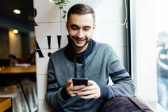 Portrait of bearded man with mobile phone in cafe. Portrait of man with mobile phone in cafe Royalty Free Stock Photography