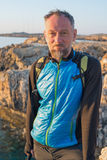 Portrait of bearded man on sea coast. Portrait of bearded man standing on a rock on sea coast. Traveler on the sea coast rests in sunny day Stock Images