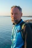 Portrait of bearded man on sea coast. Traveler on the sea coast rests in sunny morning Stock Photography