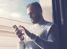 Portrait bearded man touching screen mobile phone. Man using contemporary smartphone, sunny sky background. Horizontal Royalty Free Stock Photo