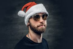 A man in Santa`s hat. Portrait of bearded man wearing Santa`s hat royalty free stock photography