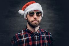 A man in Santa`s hat. Portrait of bearded man wearing Santa`s hat royalty free stock images