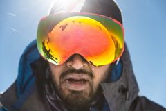 A portrait of a bearded man wearing ski goggles on his way to the top of the mountain. The concept of endurance in the. Way on the background of mountains and royalty free stock images