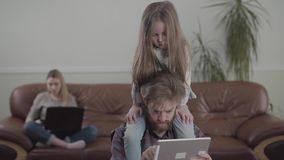 Portrait of the bearded man working with tablet close up. Little sad girl sits on fathers neck. The mother on the sofa