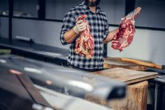 Portrait of a bearded meat man holds fresh cut meat. Portrait of a bearded meat man dressed in a fleece shirt holds fresh cut meat in a market Stock Images