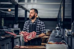 Portrait of a bearded meat man holds fresh cut meat. Portrait of a bearded meat man dressed in a fleece shirt holds fresh cut meat in a market Royalty Free Stock Images