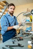 Portrait of Bearded Mechanic at Work. Waist-up portrait of talented bearded mechanic wearing checked shirt and overall posing for photography while repairing Royalty Free Stock Photography