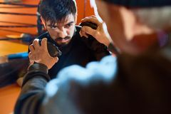 Tough Guy at Fight Practice. Portrait of bearded Middle-Eastern men boxing  with coach at practice in martial arts club, lens flare Stock Images