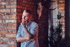 Portrait of a bearded modern male with tattoos on his arms. Royalty Free Stock Photo