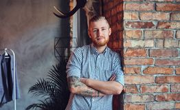Portrait of a bearded modern male with tattoos on his arms. Royalty Free Stock Images