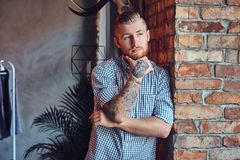 Portrait of a bearded modern male with tattoos on his arms. Stock Photos