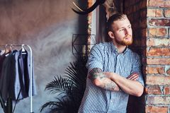 Portrait of a bearded modern male with tattoos on his arms. Royalty Free Stock Photos