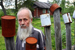 Portrait bearded old man on the background wooden farmhouse. Royalty Free Stock Photography