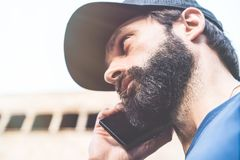 Portrait of bearded pensive man using his smartphone on the street. Blurred background. Horizontal. Visual effects. Portrait of bearded pensive man using his Stock Photo