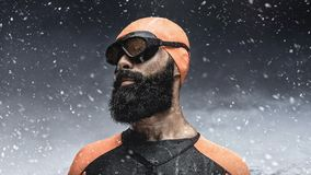 Bearded scuba diver under rain drops. Portrait of bearded scuba diver under rain drops over snow mountains background Stock Images