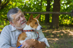 Portrait of a bearded senior man with his basenji dog Royalty Free Stock Image