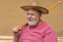 Portrait of bearded senior man in straw hat sitting against clay wall Royalty Free Stock Photo