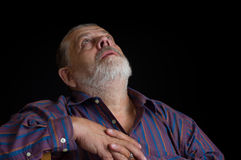 Portrait of a bearded senior man in striped shirt looking up Stock Image