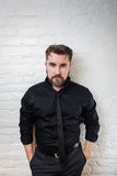 Portrait of a bearded serious man in a black shirt and tie against a white brick wall. The man is standing with his hands in his p Royalty Free Stock Photography