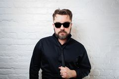 Portrait of a bearded serious man in sunglasses, a black shirt and tie against a white brick wall. The man is pulling himself by t. He tie Stock Photo