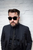 Portrait of a bearded serious man in sunglasses and a business black suit against a white brick wall royalty free stock image