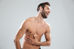 Portrait of a bearded shirtless man doubling up with laughter Stock Image