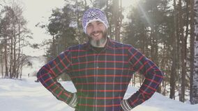 Portrait of a bearded smiling man in a winter forest looking at the camera. In a plaid shirt and hat stock footage