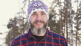 Portrait of a bearded smiling man in a winter forest. In a plaid shirt stock video
