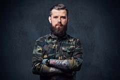 Portrait of bearded tattooed hipster male dressed in a military jacket. royalty free stock photos