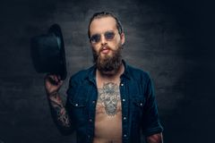 Bearded male in sunglasses and top hat. Portrait of bearded tattooed hipster male wearing a top hat over grey vignette background Royalty Free Stock Photo