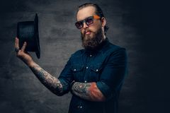 Bearded male in sunglasses and top hat. Portrait of bearded tattooed hipster male wearing a top hat over grey vignette background Stock Photos